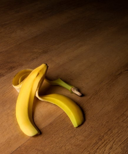 A banana skin sits on a wooden floor waiting for an unsuspecting person to slip up  : Stock Photo