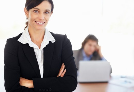 Businesswoman with blur colleague in background : Stock Photo