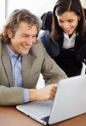 Mature businessman and woman using a laptop : Stock Photo