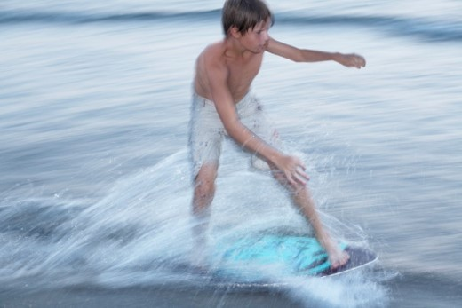 Boy skim boarding in Georgian Bay. : Stock Photo