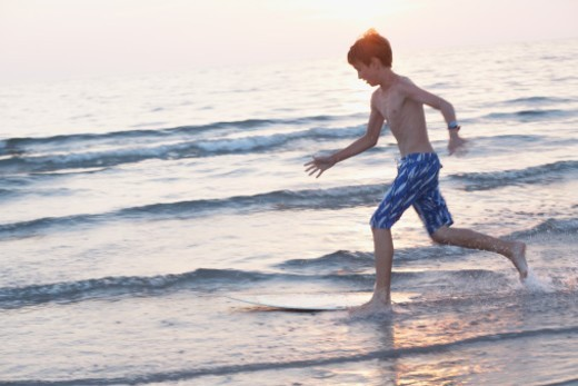 Boy skim boarding in the lake at sunset : Stock Photo