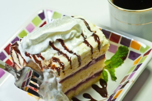 Stock Photo: 1672R-41147 This yummy white raspberry chocolate layer cake has chocolate dripped on with whipped cream.
