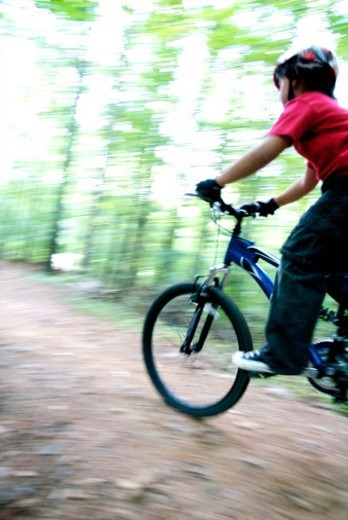 Stock Photo: 1672R-41219 Boy mountain biking at Big Creek Park in Roswell, Georgia USA
