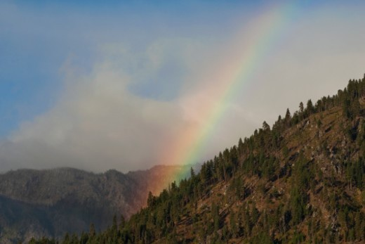 Stock Photo: 1672R-41652 A summer rainbow over the forested foothills of the Cascade Mountains in Eastern Washington. After a clearing rainstorm.