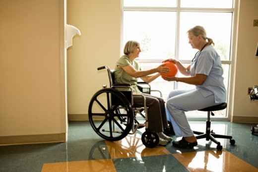 Patient in wheelchair during physical therapy treatment  with large rubber ball in gym with therapist in scrubs : Stock Photo