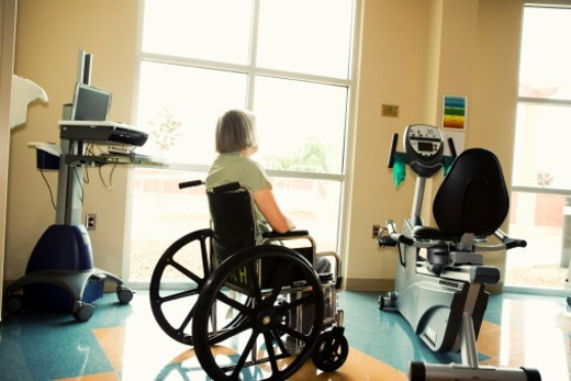 Patient in wheelchair in physical therapy gym in modern medical facility : Stock Photo