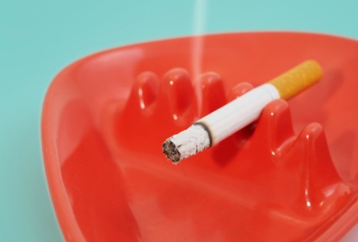 Stock Photo: 1672R-42053 Lit filter cigarette in red vintage ashtray