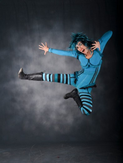excited, happy and agile female acrobat in blue body suit in mid jump : Stock Photo