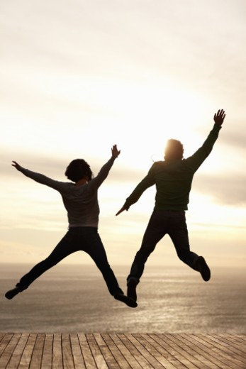 Stock Photo: 1672R-42404 Image of young couple jumping in the air with their arms raised on pier  - Silhouette