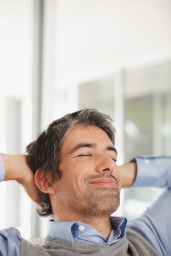 Closeup of a happy relaxed middle aged man with hands behind head : Stock Photo