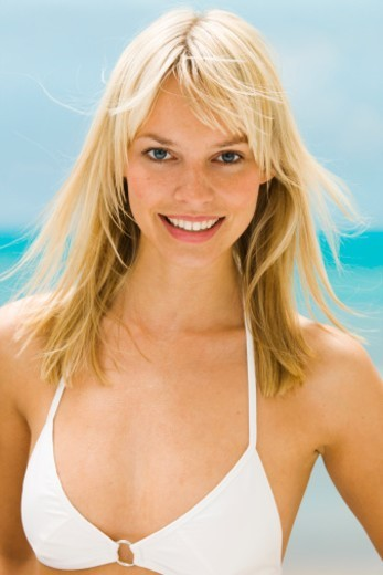 Young woman in bikini top smiling, portrait : Stock Photo