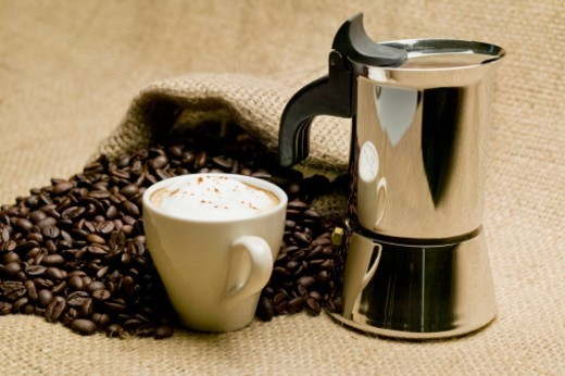 Stock Photo: 1672R-44720 Cappuccino, espresso maker and burlap sack spilling coffee beans