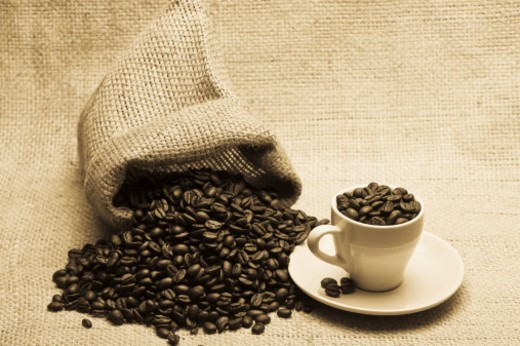 Stock Photo: 1672R-44723 Burlap sack spilling beans and coffee cup