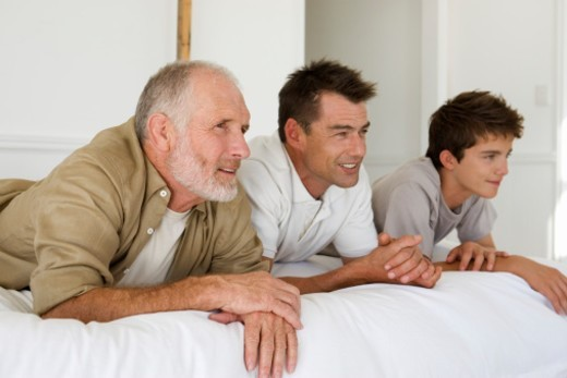 Grandfather, father and son (14-15) lying on bed : Stock Photo