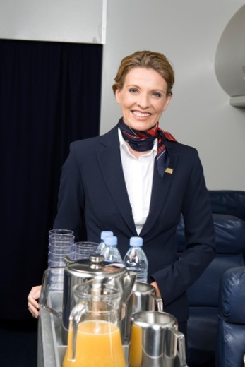 Portrait of female flight attendant serving drink : Stock Photo
