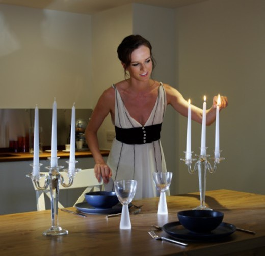 Stock Photo: 1672R-45049 a young woman, in her early twenties, lighting a candle preparing for dinner. the table is laid for a romantic meal for two. she is wearing in a black and white evening dress