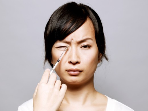 Young Asian woman receiving cosmetic surgery by injection to forehead. : Stock Photo