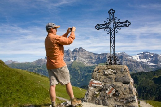 Mature man photographs iron cross marker at the Portes du Soleil summit in the Swiss Alps. The mountains visible behind him are the Dents du Midi.  This is part of the Chablais region in the canton of Valais, Switzerland. : Stock Photo