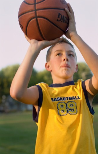 Stock Photo: 1672R-47253 Young boy about to attempt a basketball shot