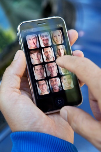 Stock Photo: 1672R-47783 Handheld device with peoples faces on display