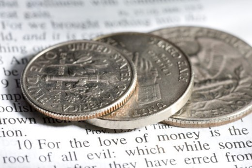 U.S. coins on a King James Bible at a verse which states that the love of money is the root of all evil : Stock Photo