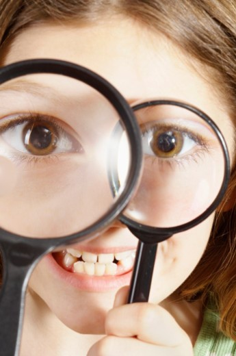 Young girl, 8 years, holding magnifying glasses up to eyes, making funny face : Stock Photo