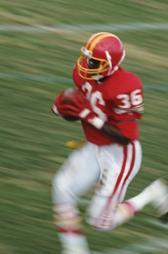 Football player running with ball (blurred motion) : Stock Photo