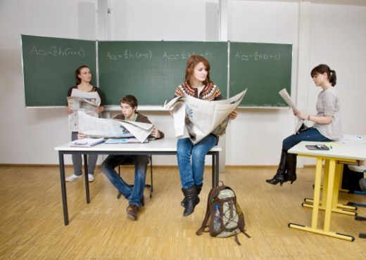 Four pupils sitting in classroom reading newspaper : Stock Photo