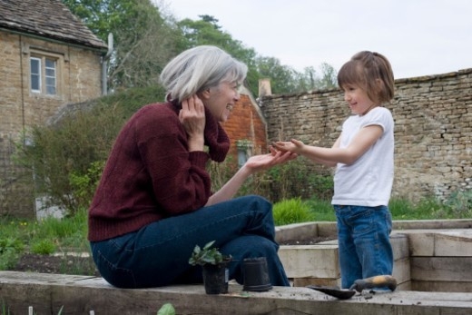Girl showing grandma dirty hands in garden : Stock Photo