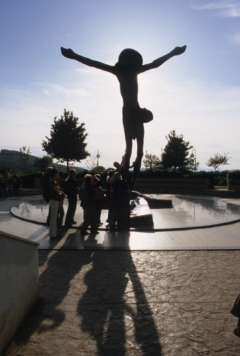People touch a bronze statue of risen Jesus Christ over empty Cross. Low view at dawn : Stock Photo
