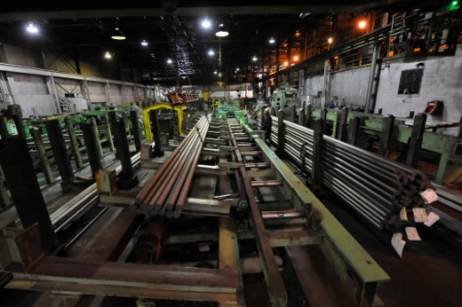 Long, huge circular 'rounds' of steel in production in cutting area of partially automated industrial, cold steel manufacturing plant (steel mill) with worker monitoring activity. : Stock Photo