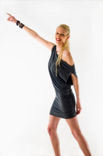 Young female Blond model mid twenties with a black evening dress pointing to her right signifying 'Follow Me' on white background : Stock Photo