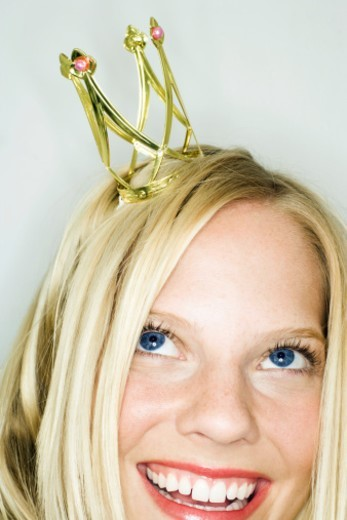 Studio shot of young woman with small crown on head, close-up : Stock Photo