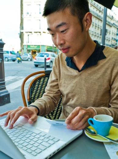 Paris, France, Young Asian Man Using Credit Card to Buy on Internet Using Laptop on French Cafe Terrace : Stock Photo