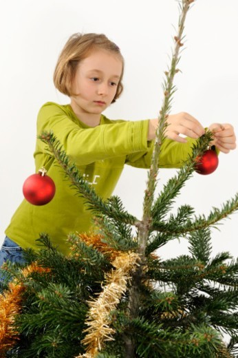Girl (8) decorating a christmas tree, France : Stock Photo