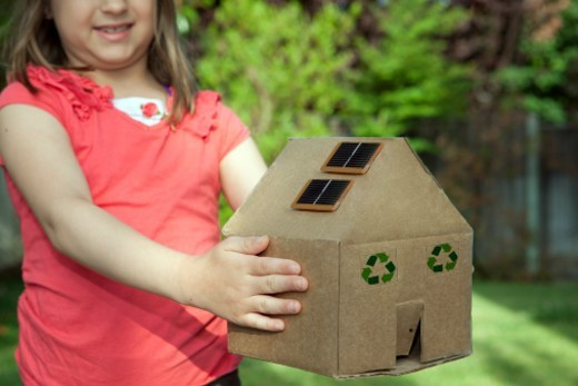 Stock Photo: 1672R-55211 Young girl holding a cardboard house with solar panels and recycling symbol on it