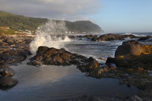 Wave crashing on rocks at sunset with tidal pool in foreground on Oregon coast : Stock Photo