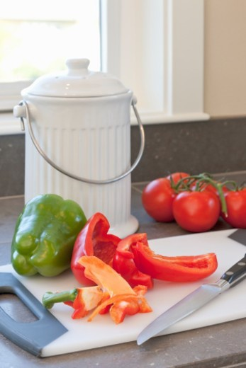 Stock Photo: 1672R-56076 Compost container and cutting board with fresh vegetables, food scraps and knife on kitchen counter