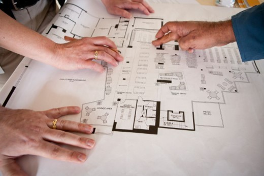 Close up of hands of woman and two men pointing at commercial building floor plans : Stock Photo