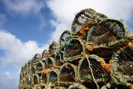 Stock Photo: 1672R-57979 pile lobster crab fishing pots blue cloudy sky