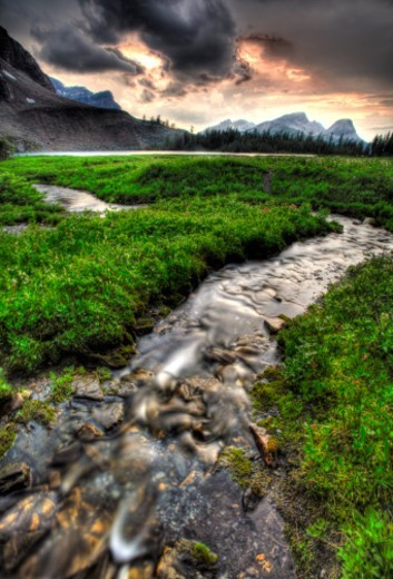 Mountain creek descends through meadow toward lake : Stock Photo