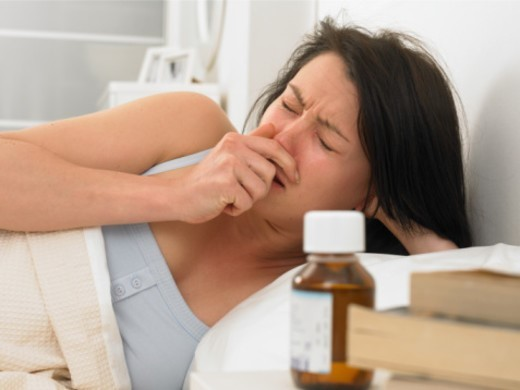 Young woman sneezing in bed : Stock Photo