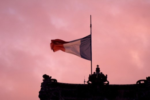 Stock Photo: 1672R-59347 The French flag in front of violet morning sky on the roof of the Louvre Palais.