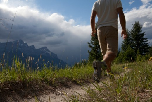 Man walks along mountain trail, oncoming storm : Stock Photo