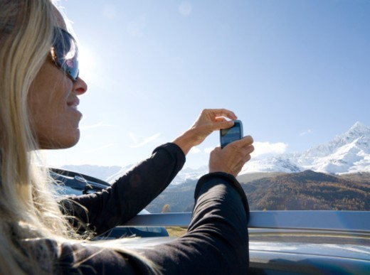 Woman takes picture of mtns from car roof : Stock Photo