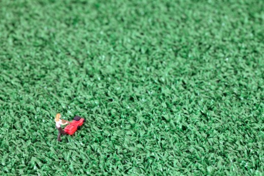 Stock Photo: 1672R-60135 Toy Figure of Woman Mowing Fake Artificial Grass