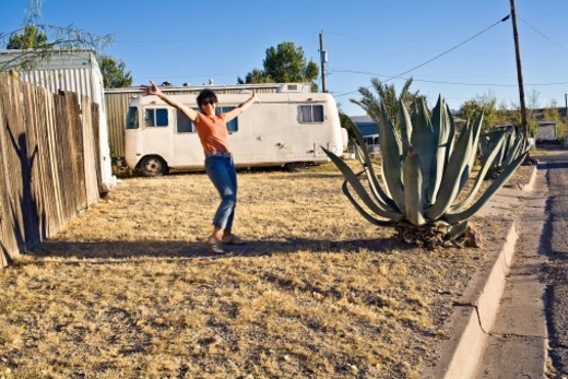 Stock Photo: 1672R-60487 Woman with arms in air standing in front of retro trailer in desert landscape