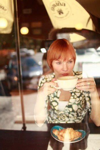 Woman sipping cafe au lait in neighborhood coffee shop and bakery : Stock Photo