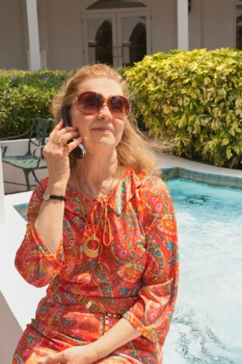Close up of Senior woman who is either traveling or retired, on cellular phone. : Stock Photo