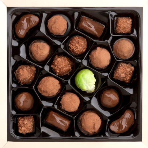 Stock Photo: 1672R-62274 An open box of chocolates in which one of high calorie sweets has been replaced by a very healthy but perhaps less tempting brussel sprout